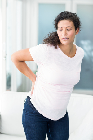 back home: Pregnant woman with back pain standing by sofa in living room Stock Photo