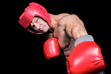 headgear: Portrait of boxer with gloves and headgear punching against black background Stock Photo