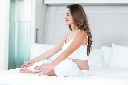 yoga pillows: Happy pregnant woman meditating on bed