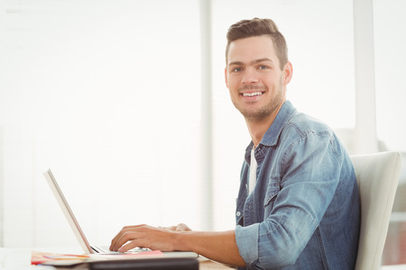portrait: Portrait of smiling young man working on laptop while sitting at desk Stock Photo