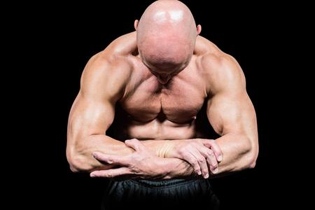 musculo: Fisicoculturista flexionando los músculos, mientras que mirando hacia abajo contra el fondo negro