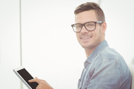 Portrait of happy man wearing eyeglasses while using digital tablet Stock Photo