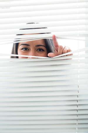peeking: Woman peeking through some window blinds against a white background