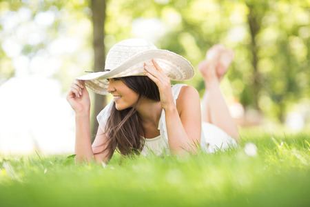 grassland: Thoughtful happy young woman holding sun hat while lying on grassland in park Stock Photo