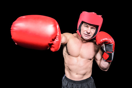 headgear: Boxer with red headgear punching against black background