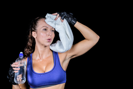 Tired woman wiping sweat while holding water bottle against black background
