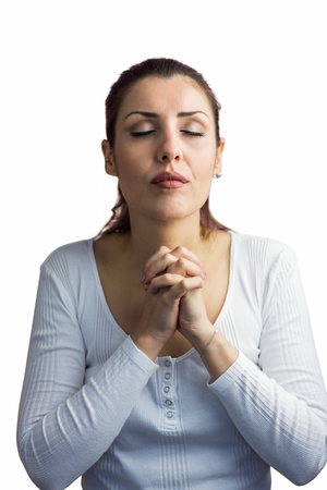 brethren: Beautiful woman praying with joining hands and eyes closed against white background Stock Photo