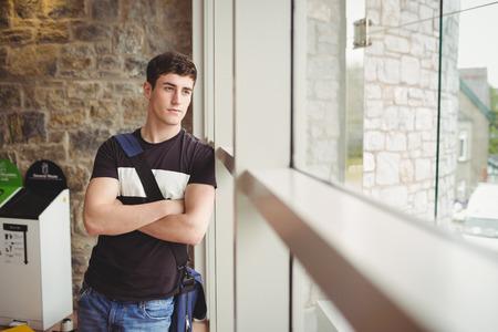 思慮深いの男子学生が大学の窓にもたれて 写真素材