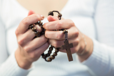brethren: Woman holding rosary beads against white background