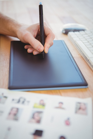 graphics tablet: Cropped hand of man drawing on graphics tablet at desk in office Stock Photo