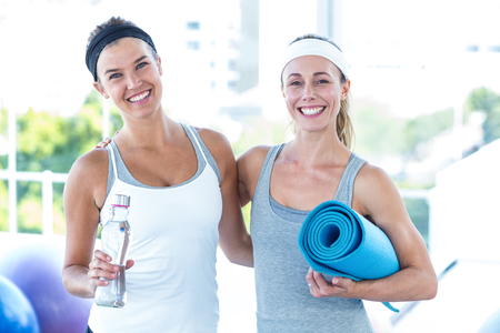 yoga mat: Portrait of women smiling while holding water bottle and yoga mat in fitness studio Stock Photo