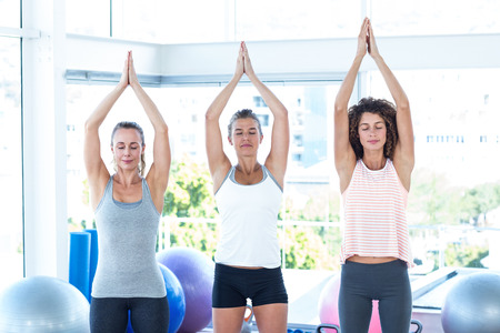 joined: Women with hands joined overhead in fitness studio Stock Photo