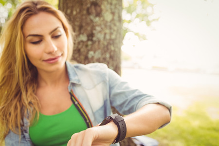 leisure wear: Smiling woman touching smart watch while sitting under tree at park