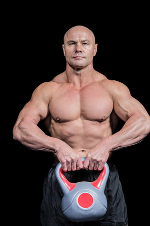 shaved head: Portrait of muscular fit man lifting kettlebell against black background