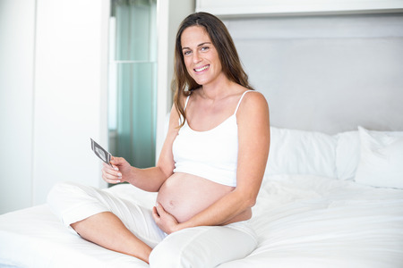 ultrasound scan: Portrait of pregnant woman with ultrasound scan sitting on bed