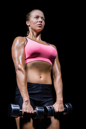free weight: Low angle view of woman exercising with dumbbells against black background