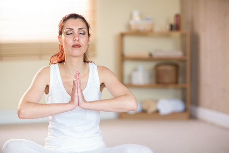 manos unidas: Mujer meditando con las manos unidas y los ojos cerrados