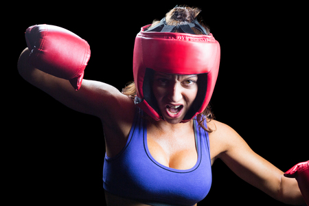fighting stance: Portrait of angry female boxer with fighting stance against black background Stock Photo