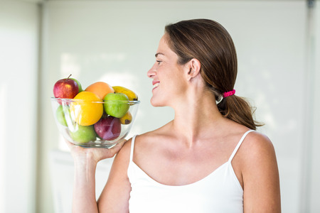 fruit bowl: Happy pregnant woman looking at fruit bowl at home