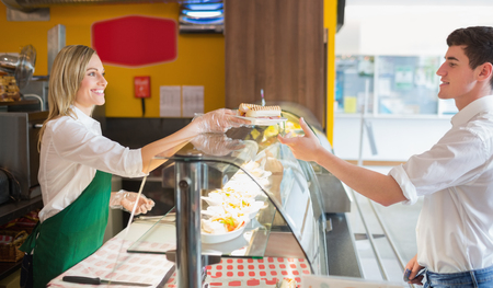 cleanliness: Female shop owner serving sandwich to male customer in bakery