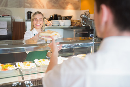 kitchen aprons: Female shop owner smiling while giving sandwich to customer in bakery Stock Photo