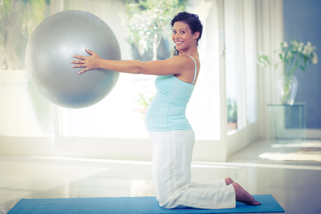 pregnant exercise: Full length portrait of smiling pregnant woman holding exercise ball at fitness studio