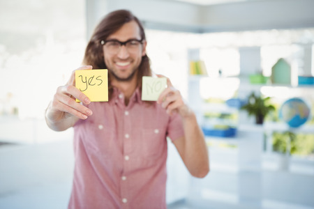 western script: Happy hipster holding adhesive note with yes sign in office