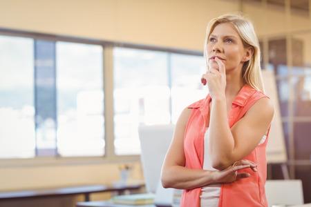 gente pensando: Reflexivo de negocios con el dedo en los labios mirando a otro lado en la oficina creativa
