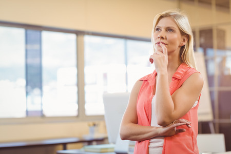creative industries: Thoughtful businesswoman with finger on lips looking away in creative office