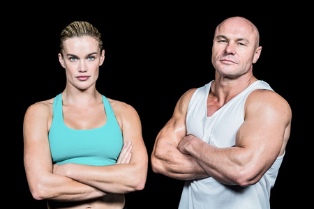 bald: Portrait of athlete man and woman with arms crossed standing against black background