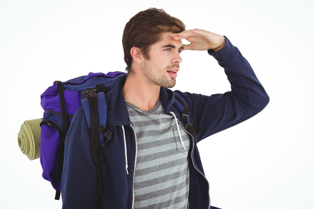 shielding: Man with backpack shielding eyes while standing against white background