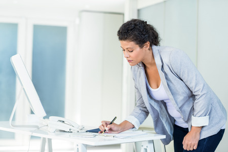 office desk: Beautiful businesswoman writing on document at desk in office