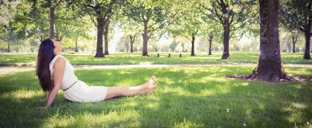 Panorama van park terwijl het jonge vrouw ontspannen op weide