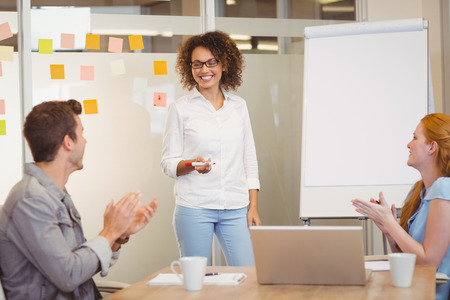 appreciating: Colleagues appreciating businesswoman of her presentation during meeting in office Stock Photo