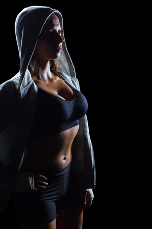 standing against: Sexy athlete in hood standing against black background