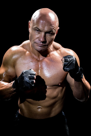 fighting stance: Portrait of muscular man with fighting stance against black background