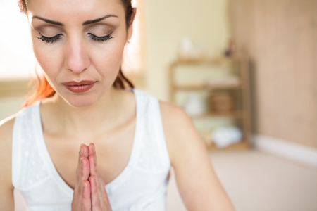 joined hands: Beautiful woman meditating with joined hands and eyes closed Stock Photo