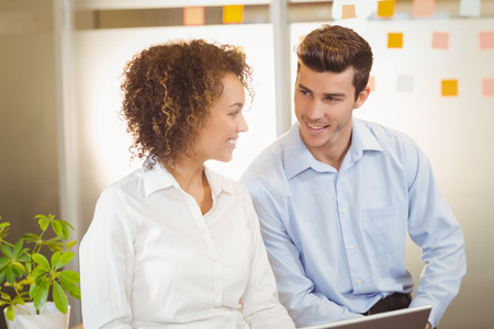 each: Smiling business people looking each other in office Stock Photo