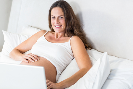 Portrait of happy woman with laptop reclining on bed Stock Photo