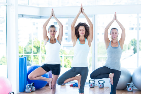 closed club: Women doing tree pose with eyes closed in fitness club Stock Photo