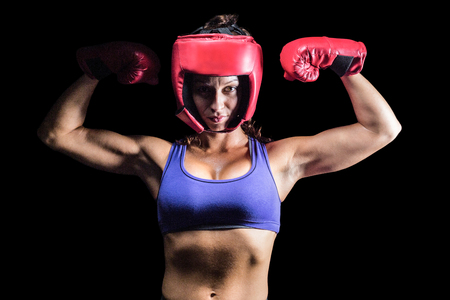 female fighter: Portrait of confident female fighter flexing muscles against black background