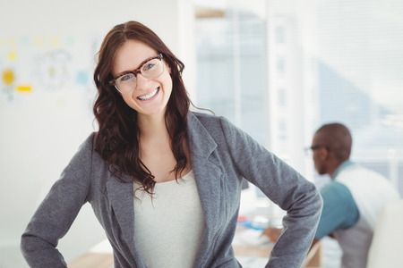 casual clothing: Portrait of smiling businesswoman wearing eyeglasses with hand on hip while standing in office Stock Photo