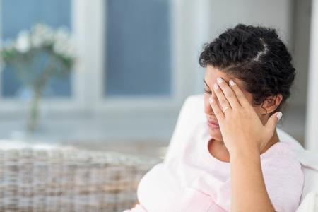 mujeres tristes: Deprimido mujer embarazada sentada en el sof� en casa Foto de archivo