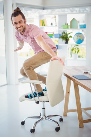 sillon: Retrato de hombre de negocios feliz de pie en la silla en la oficina