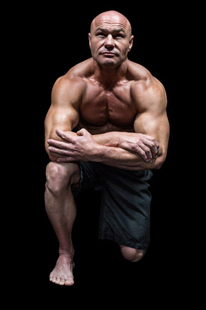 man kneeling: Muscular man kneeling down against black background Stock Photo