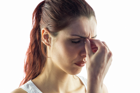 experiencing: Close-up of woman experiencing headache against white background Stock Photo