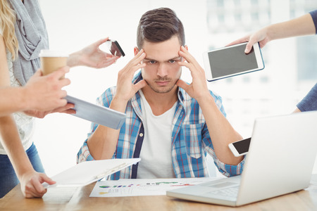 tensed: Tensed businessman with head in hand while sitting at desk