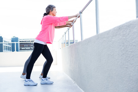railing: Women leaning on railing while exercising outdoors