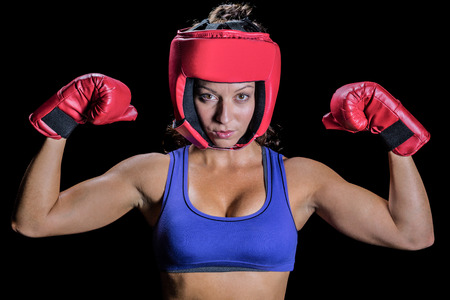 headgear: Portrait of female fighter with gloves and headgear against black background Stock Photo