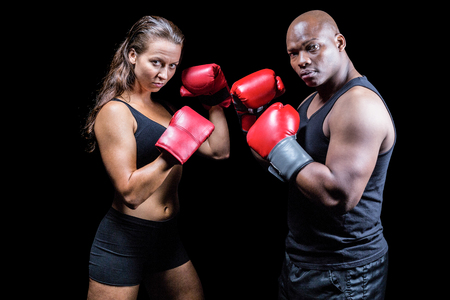 fighting stance: Portrait of male and female athletes with fighting stance against black background Stock Photo